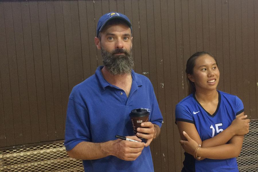 Coach Scotty Zucco, with trademark McDonald's coffee and long beard, stands on the sidelines with Seabury Hall junior Emma Pilotin. Zucco leads the Seabury Hall girls volleyball team with his belief in fundamentals of the game.