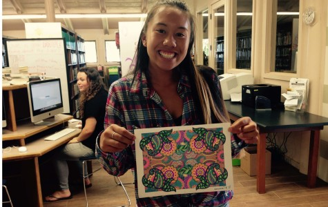 Senior Emma Pilotin shows off a page she colored during Seabury Hall's Castle Library's Library Unplugged program.